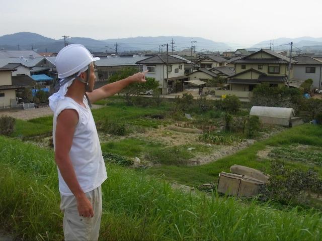 倉敷市真備町の土手に立ち、自宅の方向を眺める横溝猛さん。豪雨で水に覆われた土手と自宅の間を泳いだ
