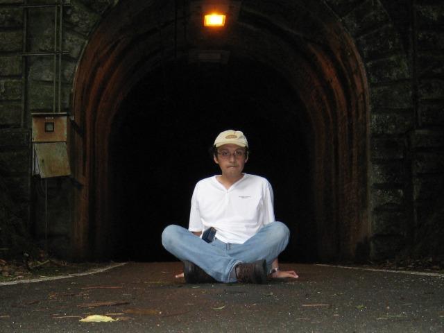 旧三瓶トンネル(愛媛県)の前で座っている花田欣也さん