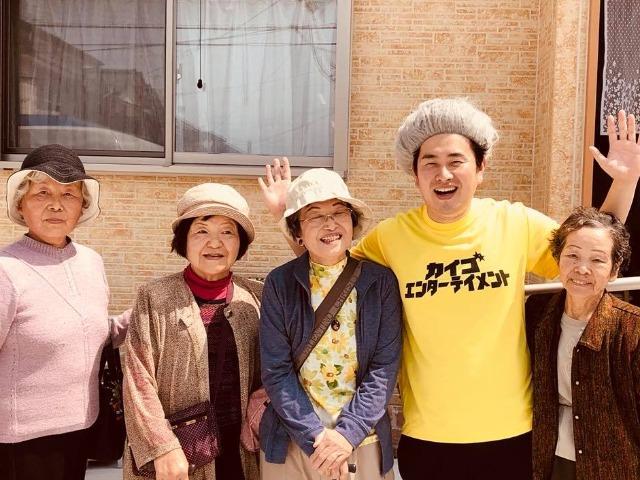 施設に通所する利用者の人たちと一緒に笑う石田竜生さん(右から2人目)
