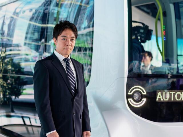 五輪選手村を走る自動運転バスの前に立つ加藤真平さん(ティアフォー提供)