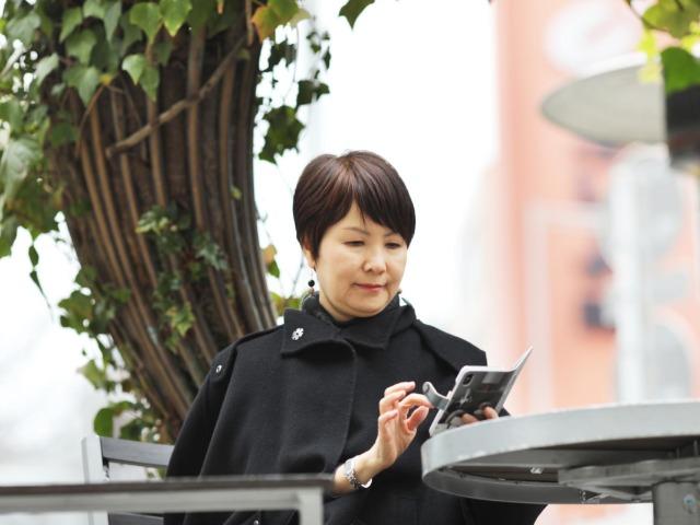 屋外でスマートフォンをさわる林理江さん