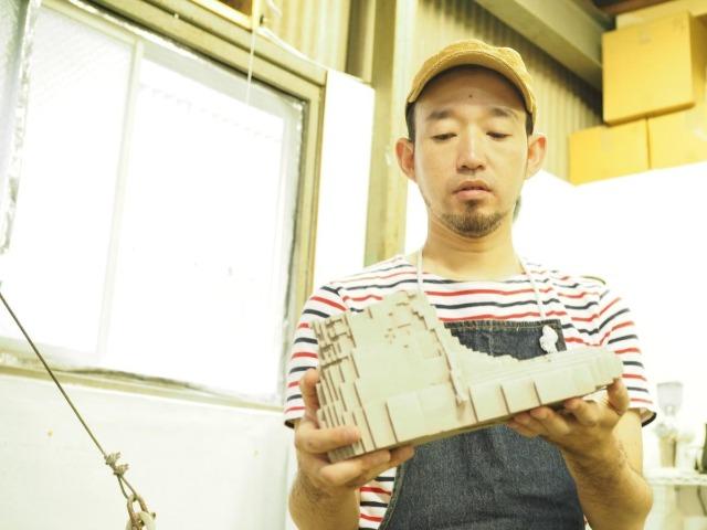 作品を手に取って見つめる増田敏也さん