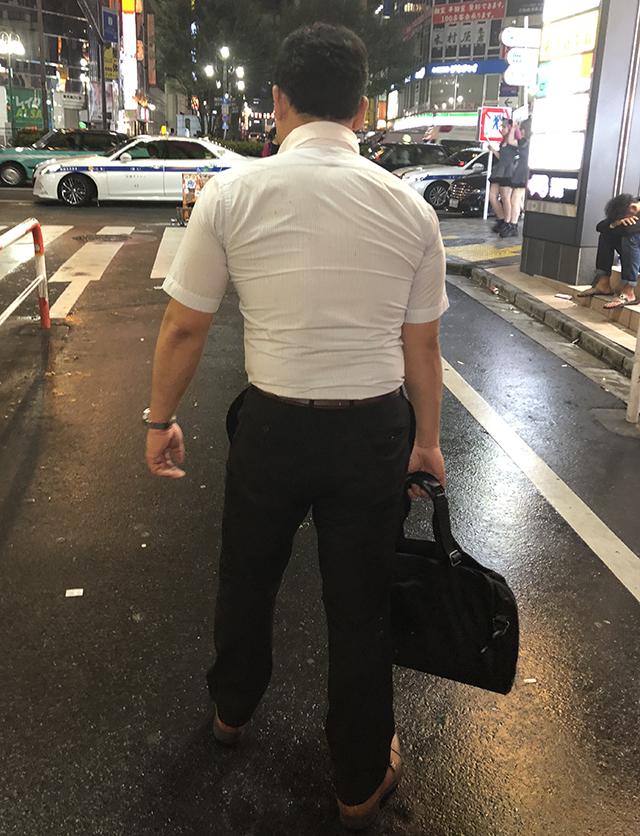 街を歩く山田さんの後ろ姿