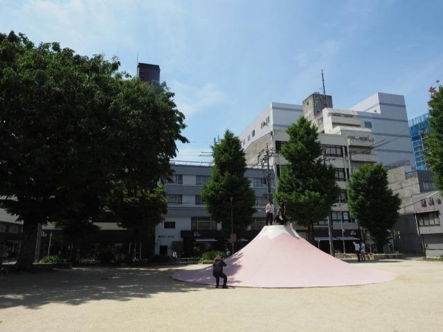 名古屋の繁華街・大須の「裏門前公園」にそびえるピンク色の富士山すべり台。北斎の浮世絵のような情趣がある
