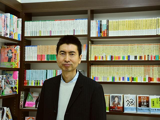 本棚の前に立つ頭木弘樹さん