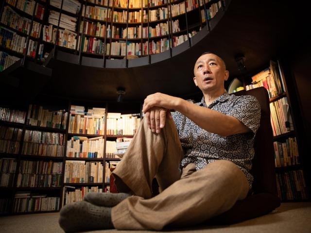 書庫でインタビューに答える松原隆一郎さん