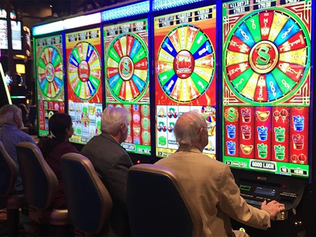 カジノでスロットマシンに向かう老人たち