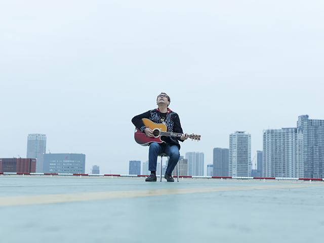 ギターを持って空を見上げる、シンガー・ソングライターの嘉門タツオさん(撮影・時津剛)