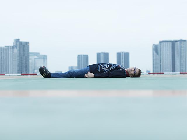 屋上であおむけなりこちらを見る、シンガー・ソングライターの嘉門タツオさん(撮影・時津剛)