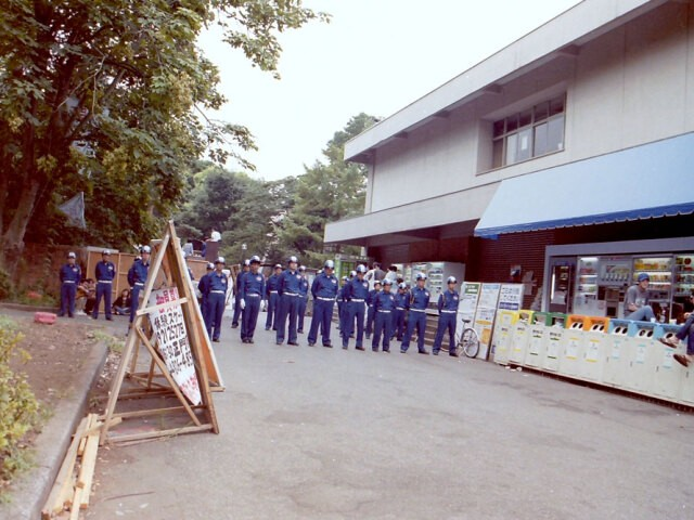 写真左手前、ガードマンが立っている前の草地部分が「テント村」建設地(駒場寮・明寮の跡地)。その向かい、大学生協の前にカップラーメンの自販機があった。(写真右部分)2001年8月撮影