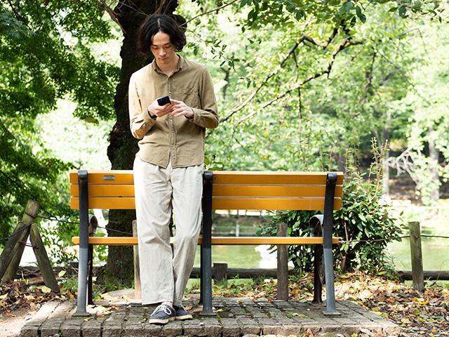 公園のベンチの前でスマホをさわる中島雄士さん(撮影:ナカニシキュウ)