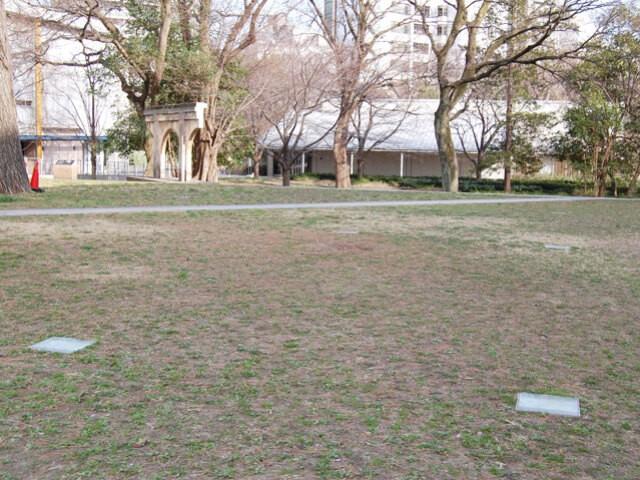 東京大学駒場キャンパス内、駒場寮跡地にあたる駒場コミュニケーションプラザ中庭。(写真左手奥)駒場寮の建物の一部が残されている。(写真手前)地面に埋め込まれた四角い照明は、駒場寮中寮の建物の柱の位置を示している。